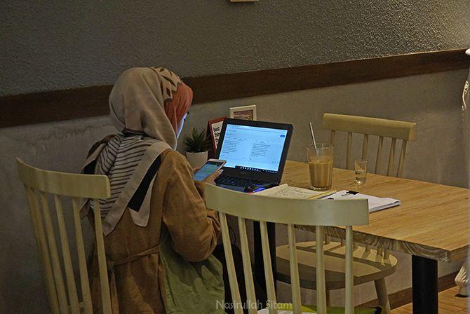 Menyendiri di kafe untuk mengerjakan tugas