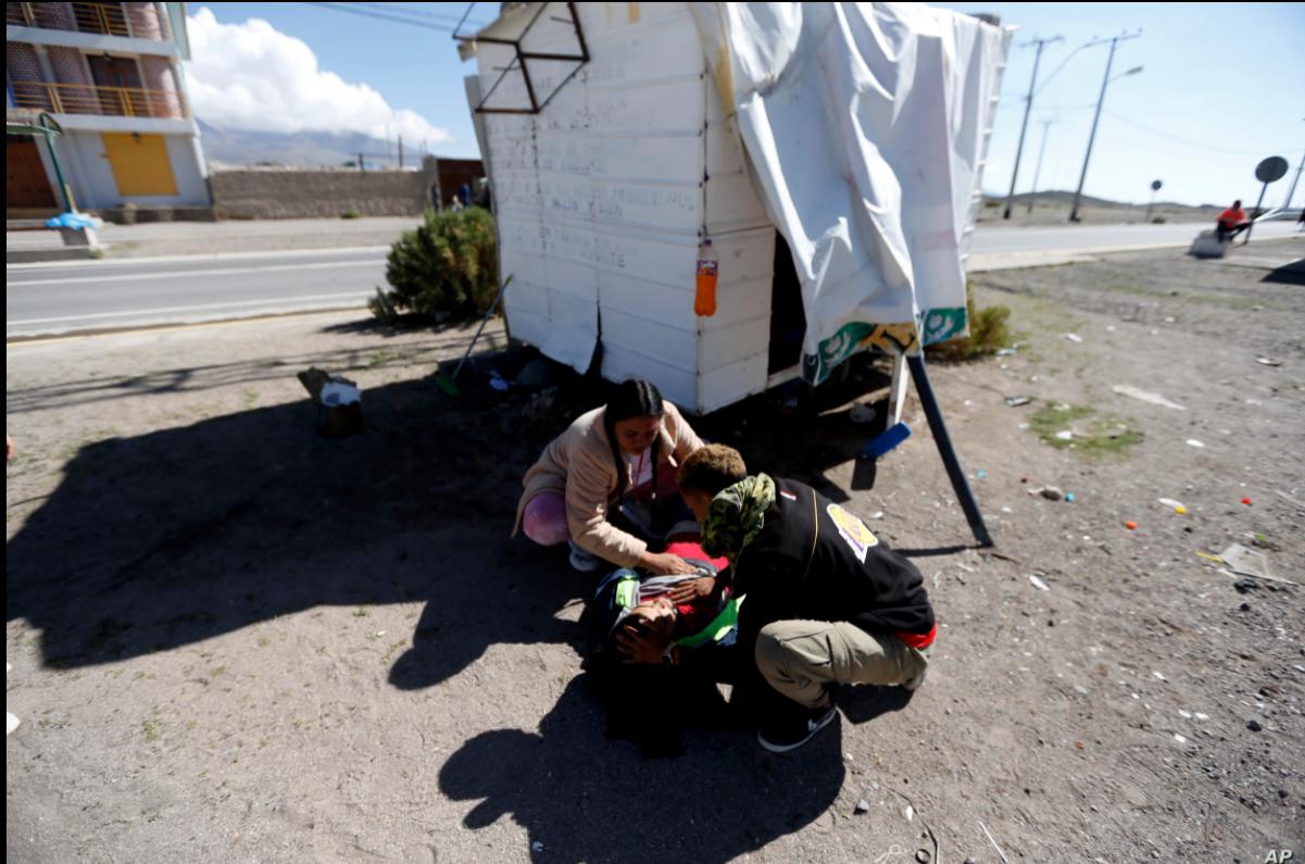 Unos migrantes venezolanos atienden a un compañero, cerca de Colchane, Chile, el 6 de febrero de 2021 / AP