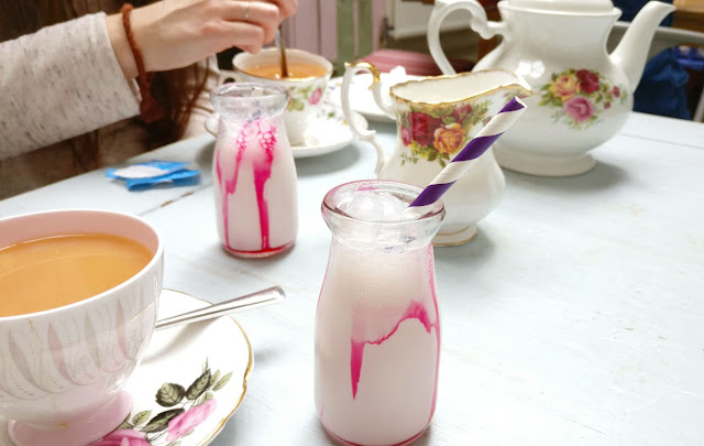 an old fashioned floral teacup, cups, and saucers, and two small glass milk bottles filled with pink milkshake and sauce