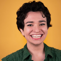 A white woman with short, curly, brown hair smiles at the camera. She wears a green shirt and is in front of a yellow background.
