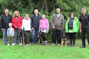 Group photo of dogs and their walkers taken outside infront of a large tree