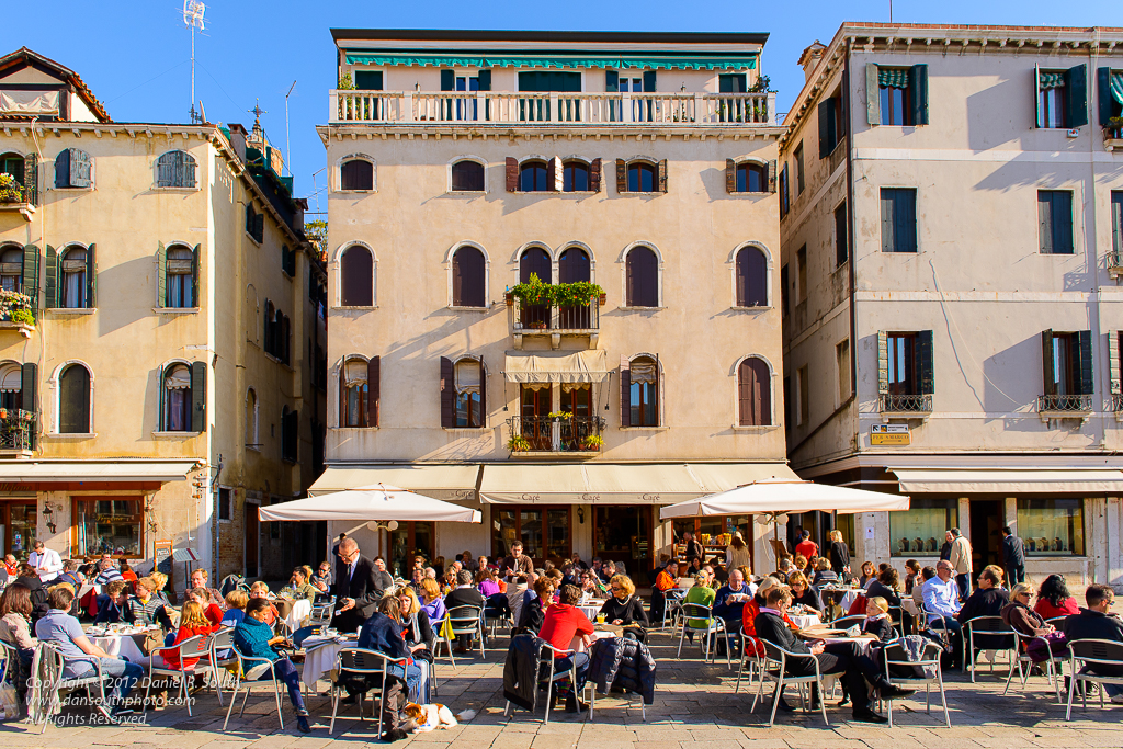 a photo of people having lunch on a sunny piazza in venice
