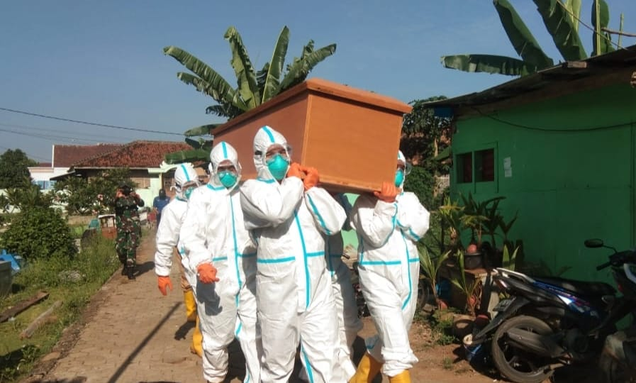 Anggota Kodim 0410/KBL Serda Antoni  Bersama Tim evakuasi Gugus Tugas Covid-19 Kota Bandar Lampung melaksakan prosesi pemakaman jenazah warga Gunung Sulah