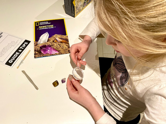 Having a closer look at the 3 gemstones found in the dig kit with the magnifying glass