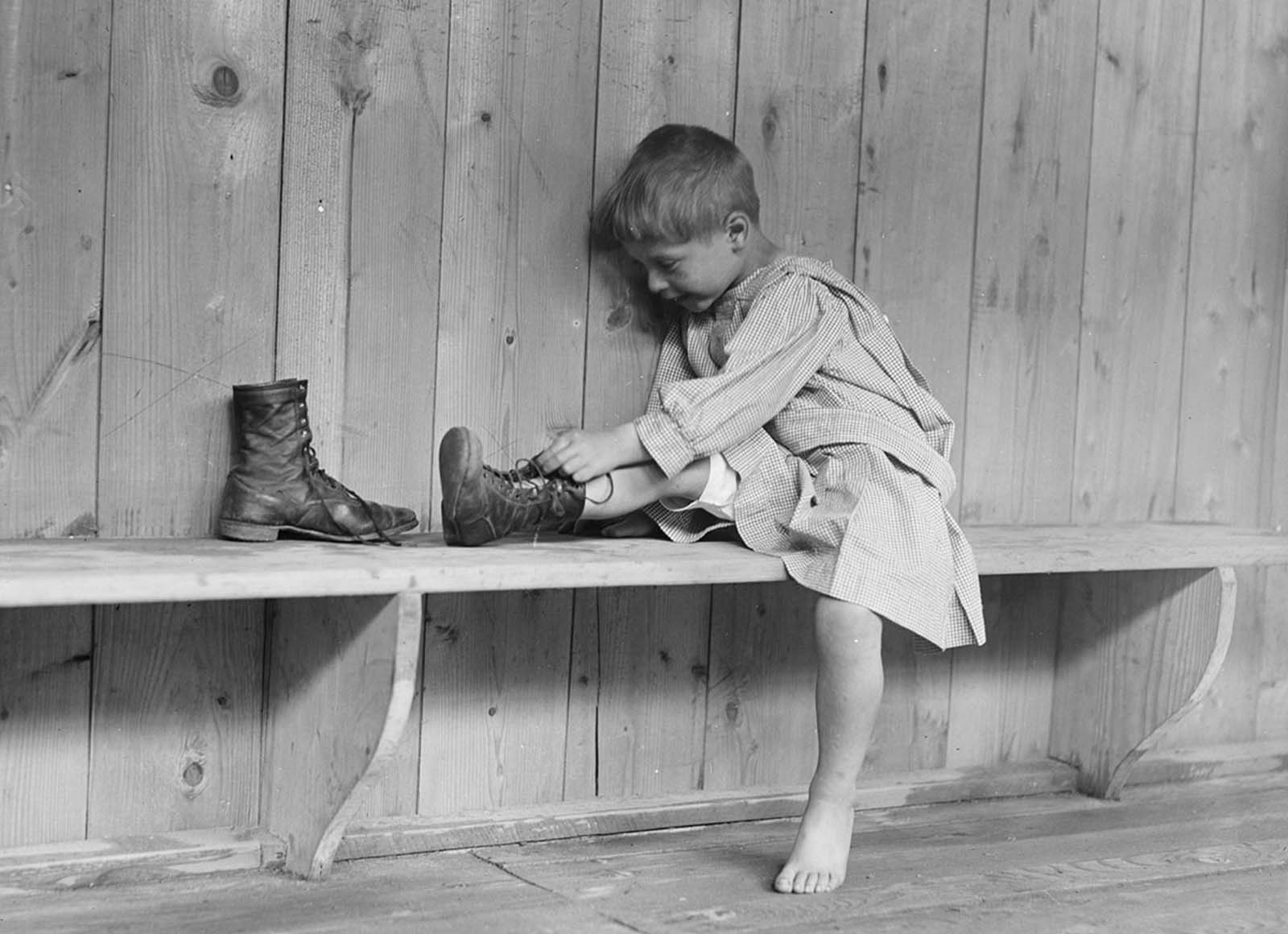 A boy puts on his new shoes at Trudeau Sanitarium, Hachette, near Paris in September of 1918.