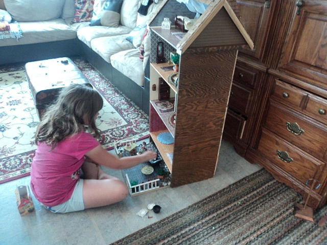 girl with homemade dresser dollhouse