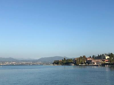 Rolig innsjø med blå fjell i bakgrunnen. En lav, grønn odde stikker inn fra høyre.