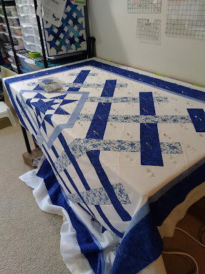 pin basting a blue and white quit draped over a table