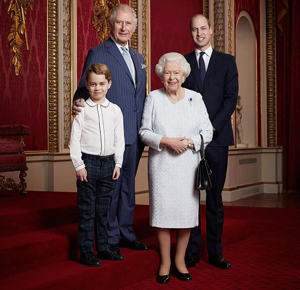 The photo shows the Prince of Wales, the Duke of Cambridge and Prince George standing with the Queen at Buckingham Palace