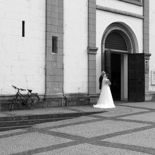 Brautpaar und Fahrrad vor der Kirche, schwarz weiß
