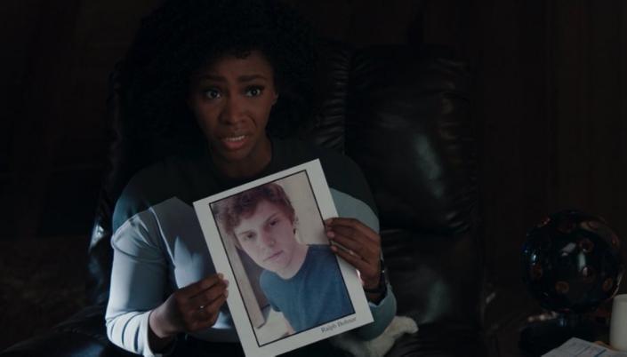 Imagem: a personagem Monica Rambeau, uma mulher negra com cabelos longos e crespos em um uniforme azul, cinza e preto, sentada em uma poltrona e segurando um papel com a foto do personagem de Evan Peters em sua forma humana e o nome Ralph Bohner embaixo.