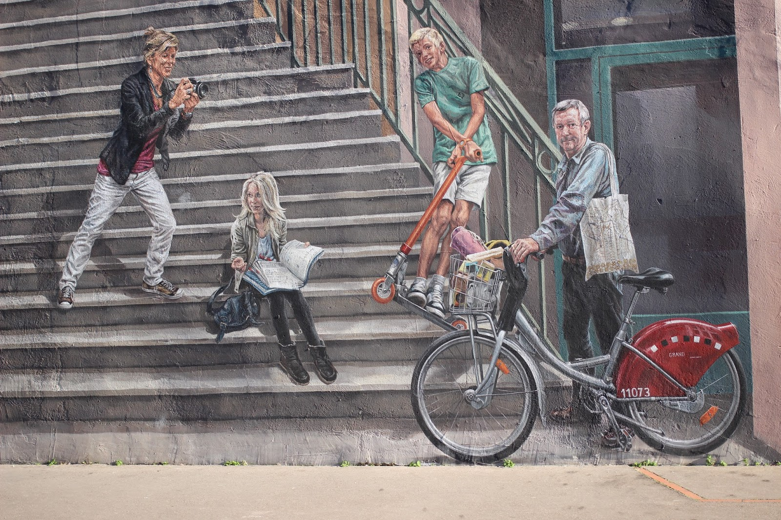 painting of stairs on building man on bike taking pictures woman