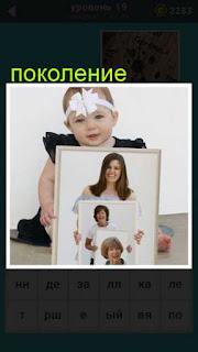 сидит девочка и в руках у неё несколько фотографий в рамках с разными поколениями женщин