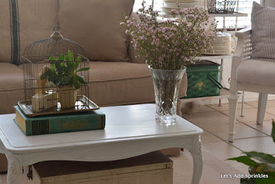 green grainsack that is vintage, waterford vase, brass bird house with marble parrot bookend on white table.