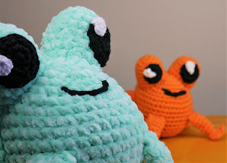 Two crochet frogs, one with fluffy yarn in pastel green very close to the camera, the second much smaller and with orange cotton yarn in the background.