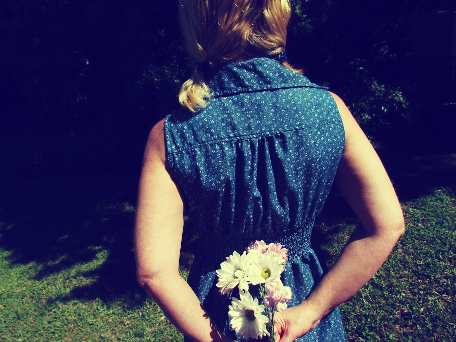 Gloom and Glow Mood Lighting of Woman in Blue Denim Dress Holding Flowers While Facing a Nature Background