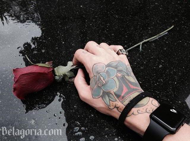 Una mano de hombre tatuada recogiendo una rosa de un charco