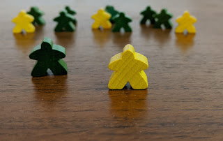 Several meeples, wooden playing pieces in stylised human form, on a wooden tabletop. Most are green, some are yellow. One of each colour is in the foregroud, while those in the background are out of focus. The yellow foreground meeple is slightly further forward and more in focus than the green foreground meeple.
