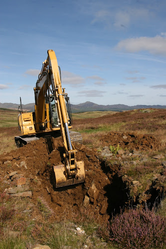 A digger creates a trench in a rural area of Scotland
