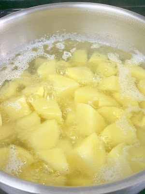 Potatoes boiling on a pot of water