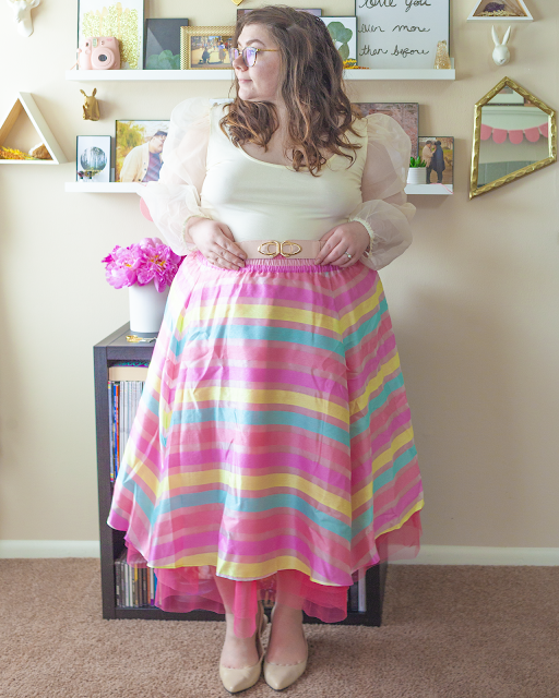 An outfit consisting of a sheer balloon sleeve white blouse tucked into a pastel pink, yellow and blue tulle and organza midi A-line skirt and beige slingback heels.