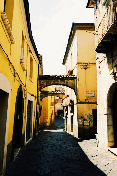 An alley with cobbled stones and bright yellow buildings in Benevento