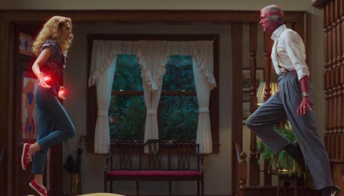 Imagem: Wanda e Visão flutuando em pleno ar em sua sala, ele em sua forma sintezóide com a pele metálica e vemelha com detalhes verdes, vestindo por cima uma camisa branca, jeans e suspensórios e ela conjurando uma energia vermelha em suas mãos.