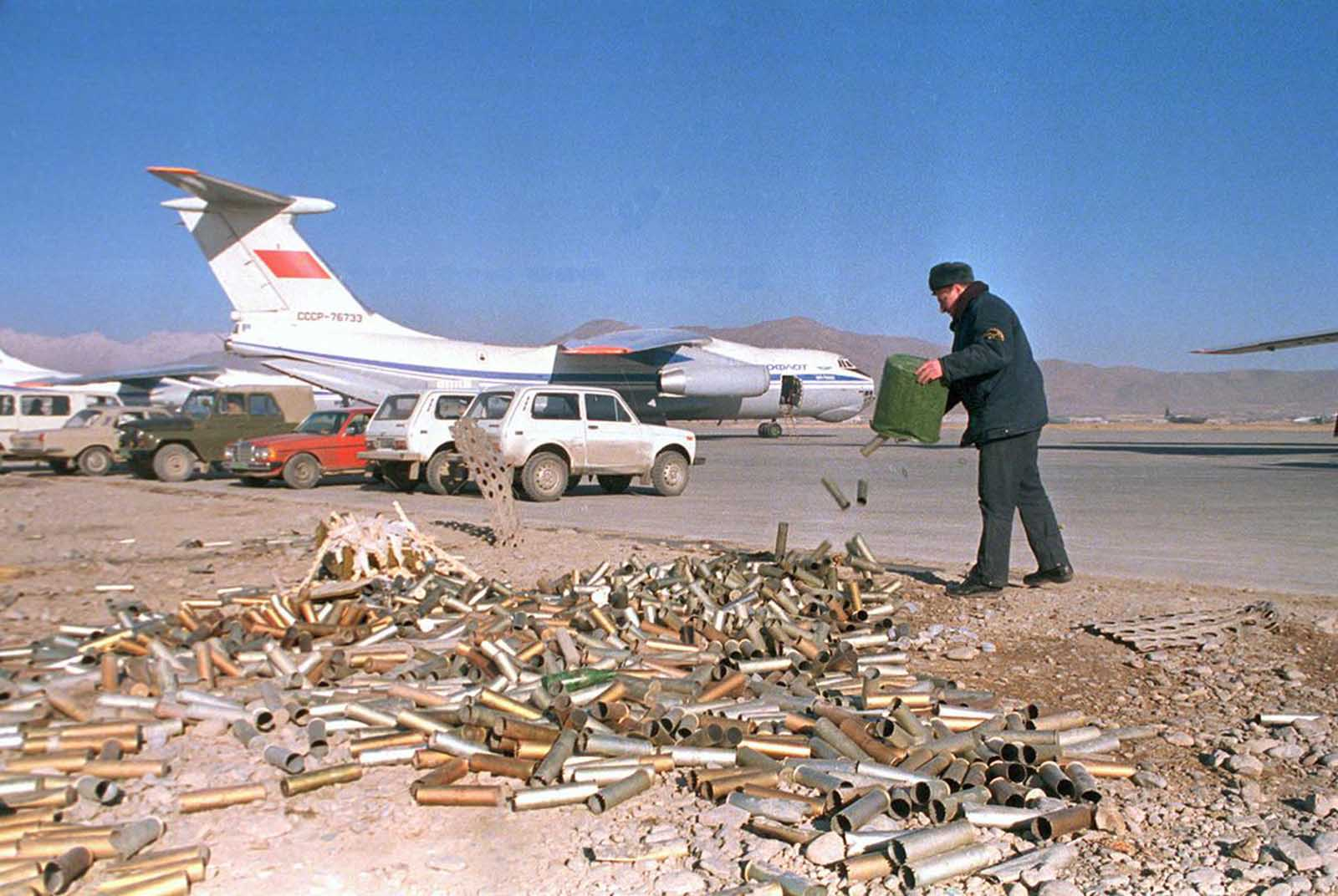 A Soviet air force technician empties a bucket of spent flare cartridges at the Kabul airbase on January 23, 1989.