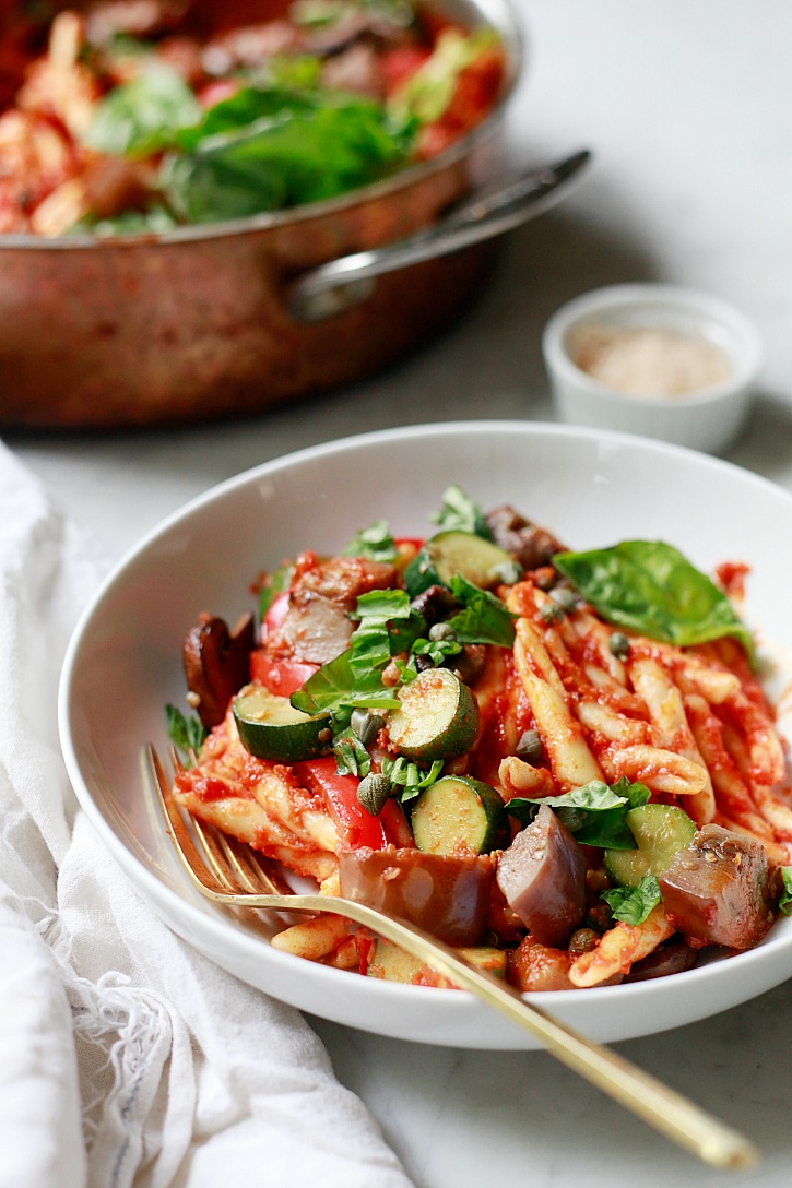 Easy one pan vegetarian pasta with marinara, eggplant, mushrooms, zucchini, basil, and capers.