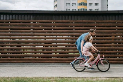 A man helping a kid ride a bike
