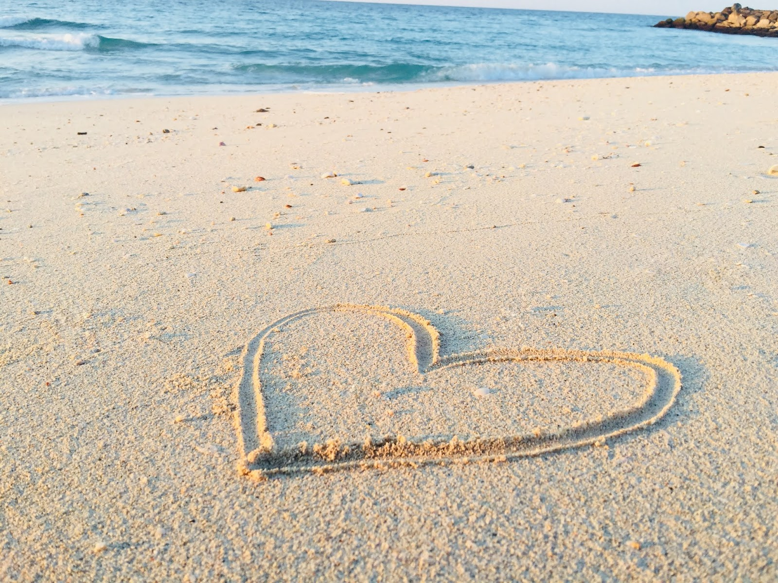 Hand made heart shape on beach sand image