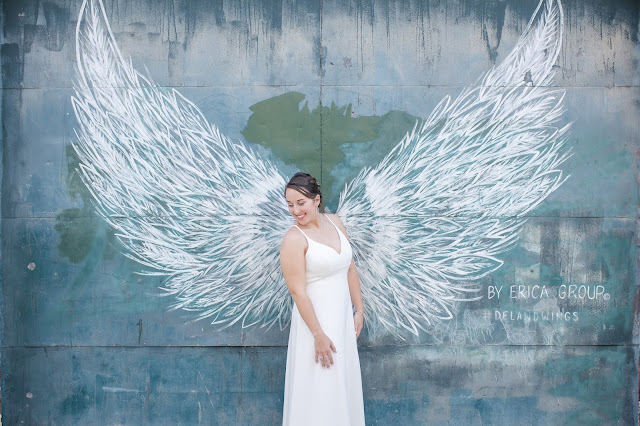 bride in white dress in front of wall with wings