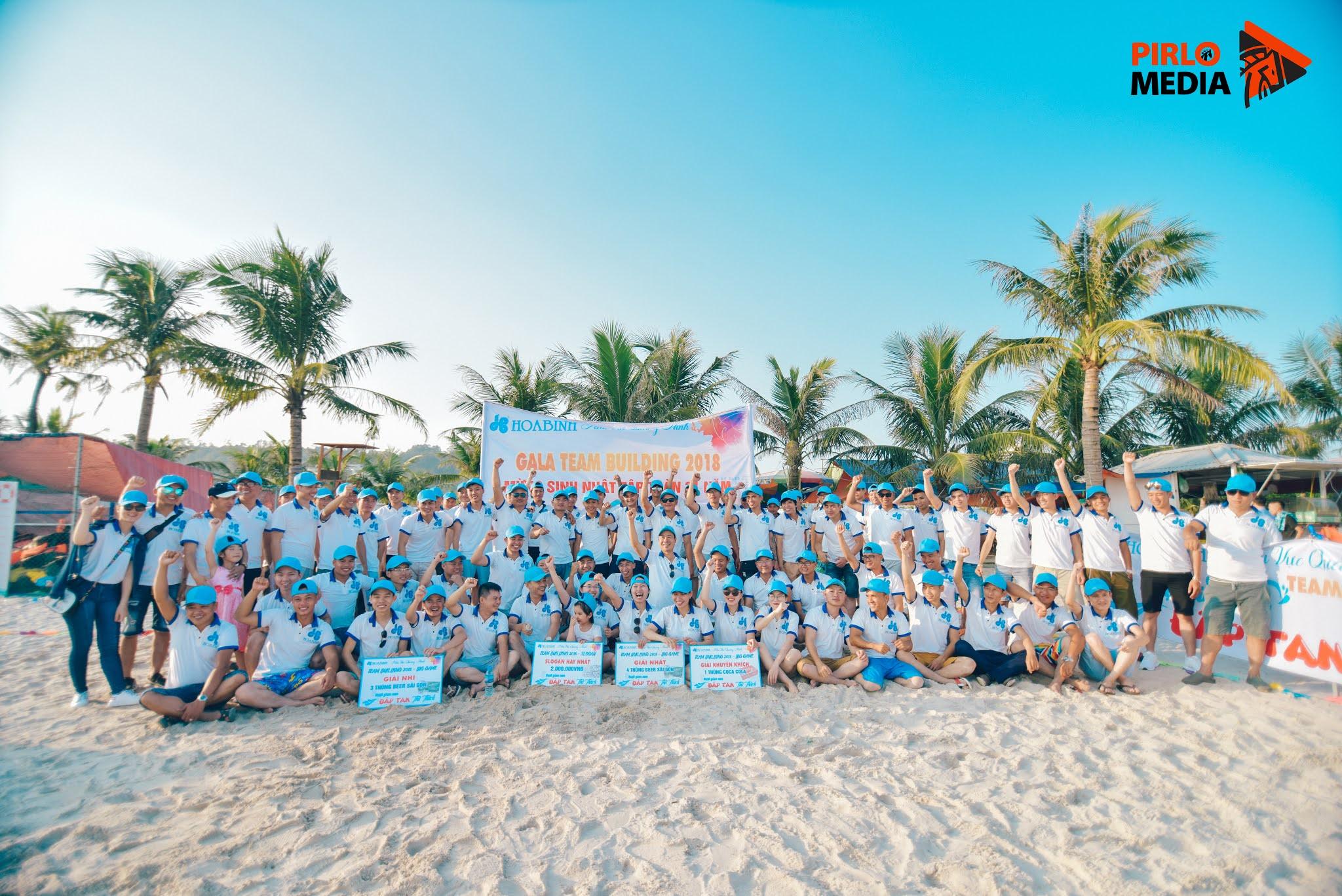 Chup ảnh flycam teambuilding tai Hạ Long, mọi người đội mũ cùng nhận thưởng trên bãi cát