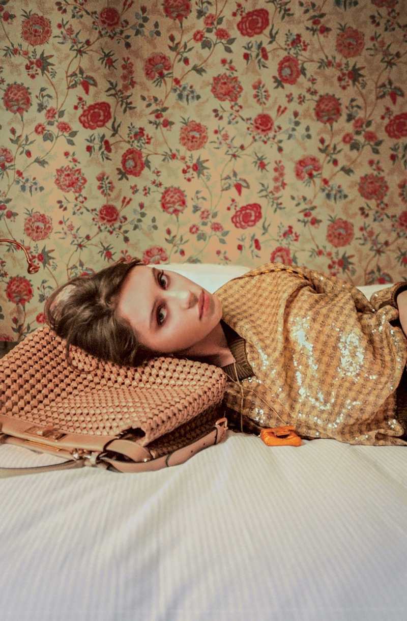Posing in bed, Iris Law models alongside Peekaboo bag.