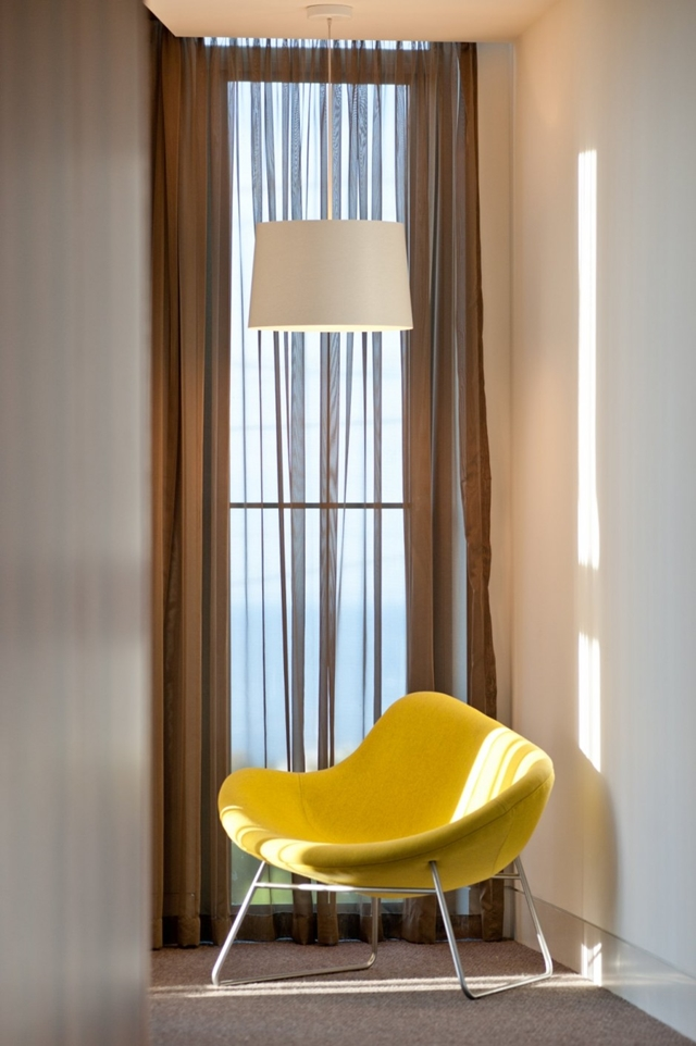 Yellow chair by the window in Hill House by Rachcoff Vella Architects