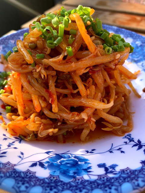 Chilli bean sprouts on blue and white plate at TOLA Peckham