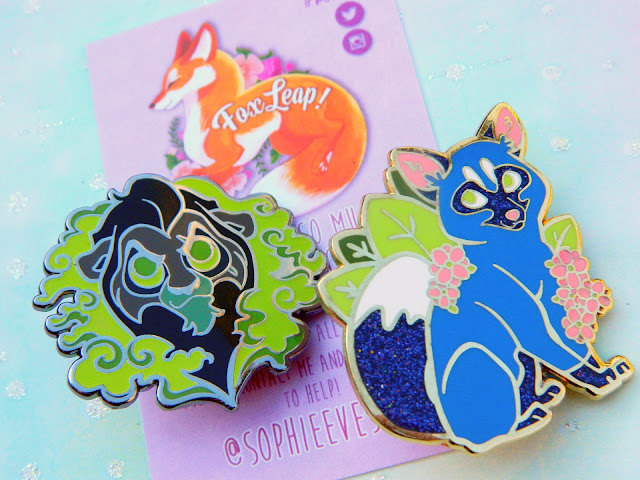 A photo of two beautiful enamel pins by FoxLeap, one is Lion Kings Scar and the other is a blue fox