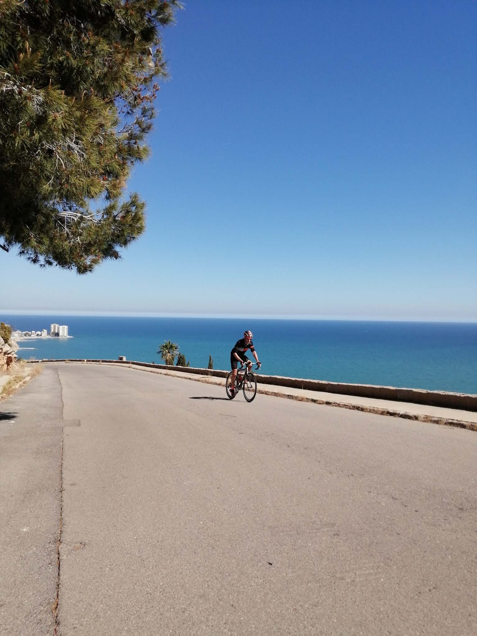 Cyclist climbing with Mediterranean Sea in background