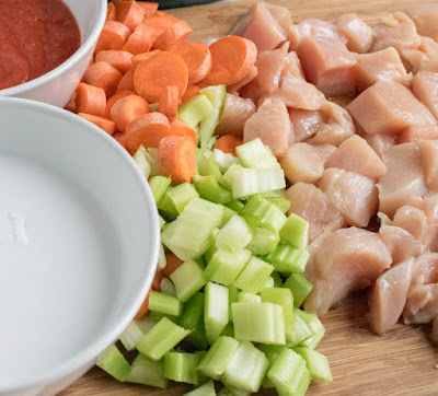 cutting board with diced celery, carrots and chicken