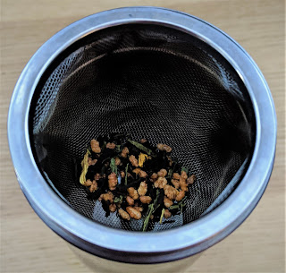 A circular mesh next that fits over the mug and filled with tea.