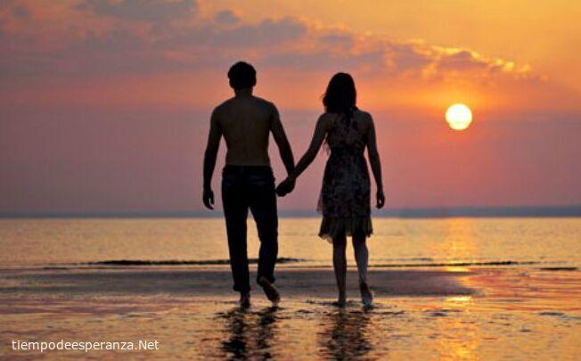 Pareja de enamorados caminando por la playa tomados de la mano