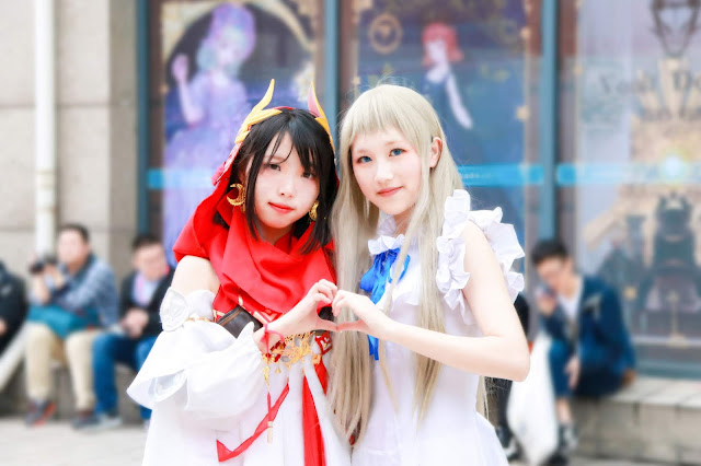 two anime cosplayer girls making a heart sign