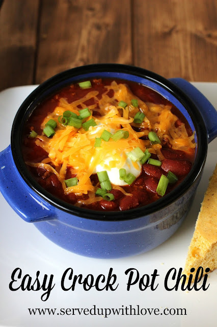 homemade chili with beans in a blue bowl on a white plate covered with sour cream and cheese