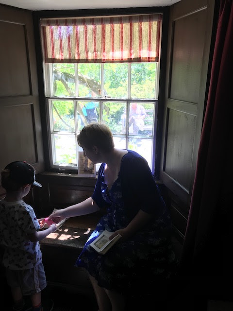 Mum and son in front of an old window looking at books