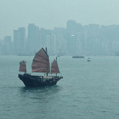 a chinese junk boat sailing in Victori Harbour, Hong Kong, with city in background