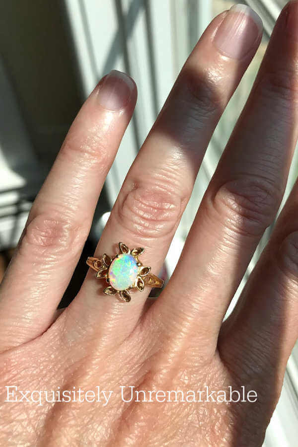 Yellow gold Opal Ring on woman's ring finger.