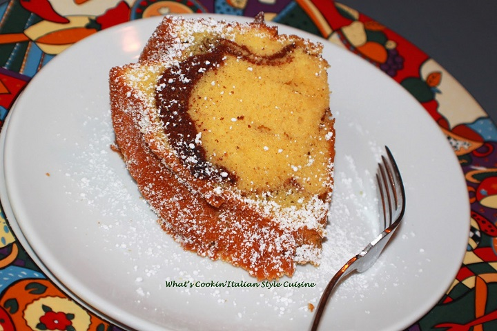 this is a marble made from scratch pound cake on a white plate dusted with powdered sugar