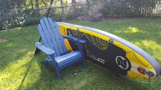 paddle board and Adirondack chair in the summer sun