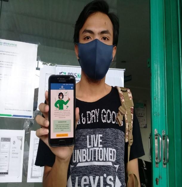 """Mojokerto -Corona Virus Disease2019 atau lebih sering dikenal dengan Covid-19, merupakan wabah virus yang penyebarannya telah merambah ke seluruh penjuru dunia. Untuk mengatasi penularan virus Covid-19 bagi peserta Jaminan Kesehatan Nasional – Kartu Indonesia Sehat (JKN-KIS), BPJS Kesehatan telah menambahkan fitur terbarunya pada aplikasi Mobile JKN berupascreeningCovid-19.  Peserta JKN-KIS dapat dengan mudah mengetahui apakah kondisi tubuhnya dalam keadaan yang normal atau cenderung lebih mendekati gejala Covid-19cukup dengan melakukandownloadaplikasi Mobile JKN, kemudian peserta dapat melakukanscreeningsecara gratis. Hasil dariscreeningCovid-19tersebut bisa langsung menggambarkan kondisi seseorang dengan menilai potensi rendah atau tingginya terpapar Covid-19.  Fitur baru yang terdapat di Mobile JKN juga telah dirasakan manfaatnya oleh salah satu peserta, Emil Zuis yang berasal dari Mojosari Kabupaten Mojokerto.  """"Saya merupakan peserta Pekerja Bukan Penerima Upah (PBPU), sudah sekitar beberapa bulan yang lalu saya telah mempunyai aplikasi Mobile JKN dan saya merasa sangat dipermudah dengan fitur-fitur yang telah ada pada aplikasi tersebut,"""" ungkapnya  Kemudahan fitur ini dapat diakses oleh semua kalangan. Peserta akan disuguhkan beberapa pertanyaan beserta pilihan-pilihan di dalamnya. Pertanyaan tersebut lebih mengacu kepada gejala-gejala yang diderita oleh peserta selama 14 hari dan peserta juga akan disuguhkan beberapa riwayat pernyakit yang diderita untuk lebih memastikan hasil akhir dariscreeningtersebut lebih mengarah ke hasil yang rendah atau tinggi akan terpaparnya Covid-19.  Jika hasilnya tinggi, maka peserta akan diinformasikan untuk segera periksa ke Fasilitas Kesehatan Tingkat Pertama (FKTP) yaitu Puskemas, klinik yang kerjasama dengan BPJS Kesehatan atau Dokter keluarga yang telah dipilihnya. Namun sebaliknya jika menunjukkan hasil yang rendah, peserta akan diarahkan untuk rajin-rajin menjaga kebersihan dengan cara mencuci tangan dengan sabun dan air """