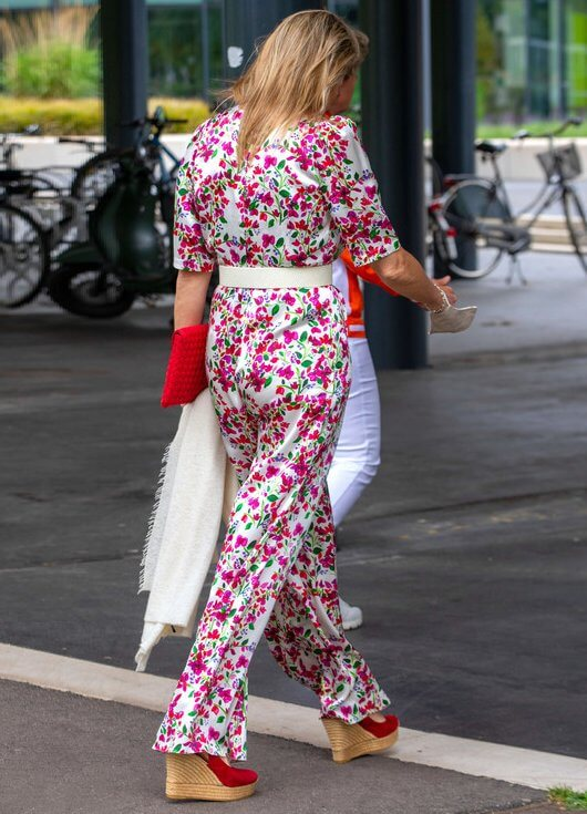Queen Maxima wore a floral print silk satin half sleeve wide leg jumpsuit from Seren. She wore red wedges from Tory Burch
